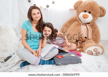 Portrait of two beautiful smiling sisters sitting in children room together - stock photo