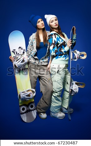 portrait of two beautiful sporty girls with snowboards on blue - stock photo