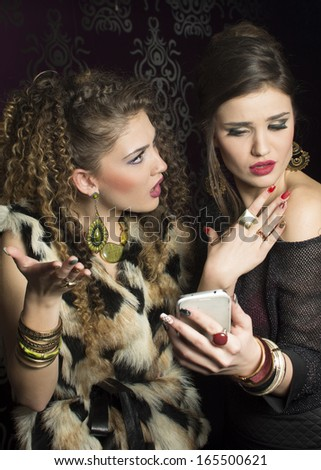 Portrait of two beautiful surprised girls looking at cellphone