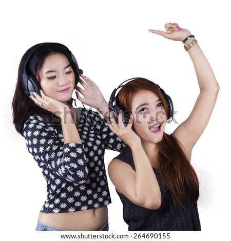 Portrait of two beautiful teenage girls dancing while listening music with headphones, isolated over white - stock photo