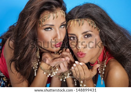 Portrait of two beautiful young brunette woman posing over blue background.