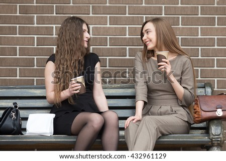 Portrait of two beautiful young girlfriends sitting on bench outdoors and talking with happy smiles. Successful attractive women friends holding paper cups of coffee and chatting during break time - stock photo