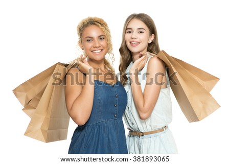 Portrait of two beautiful young girls standing smiling happily holding paper bags after a good shopping, isolated on white background - stock photo