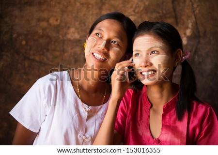 Portrait of two beautiful young traditional Myanmar girls using smart phone. - stock photo