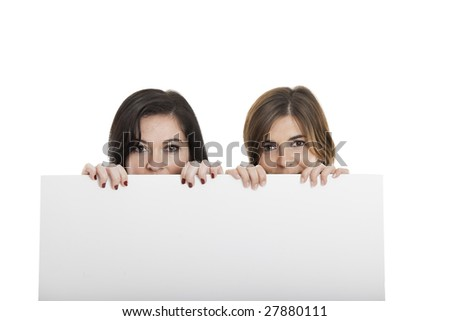 Portrait of two beautiful young women holding a blank notecard. - stock photo