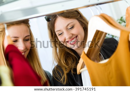Portrait of two beautiful young women shopping in a clothes shop. - stock photo