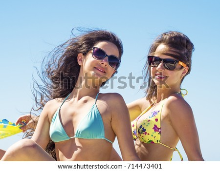 Portrait of two beautiful young women sitting by sea on pier enjoying summer sunny day Fun, recreation - concept.
