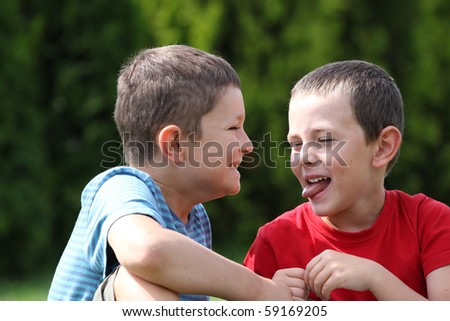 Portrait of two boys, siblings, brothers and best friends giggling and making faces. - stock photo