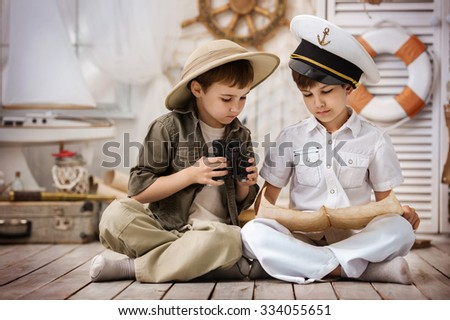 Portrait of two boys - traveler and sailor - with globe and binoculars in his playroom - stock photo