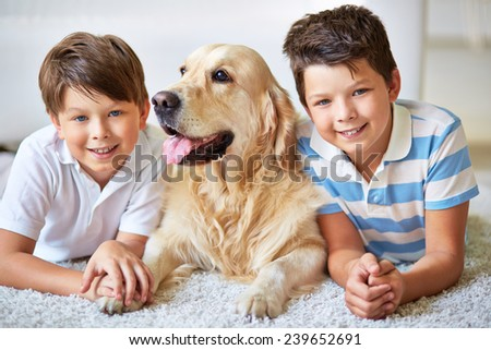 Portrait of two brothers with dog looking at camera - stock photo