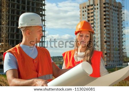 Portrait of two builders standing at building site - stock photo