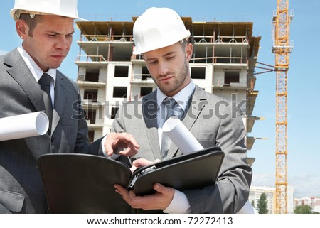 Portrait of two builders standing at building site and discussing new project held by one of them - stock photo