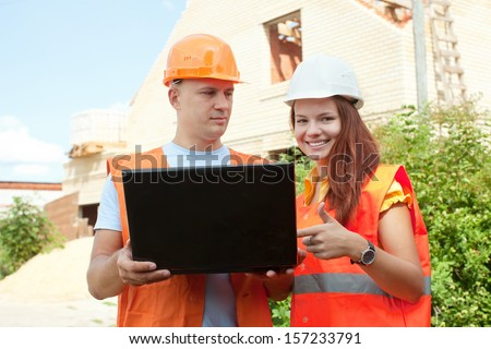 Portrait of two builders works at building site  - stock photo