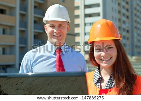 Portrait of two builders works at construction site  - stock photo