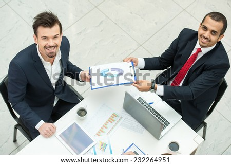 Portrait of two business men are discussing papers at meeting. They are looking at the camera. - stock photo