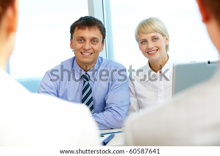 Portrait of two business partners looking at their interviewees during conversation - stock photo