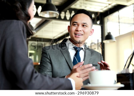 portrait of two business people discussing new project while coffee break - stock photo
