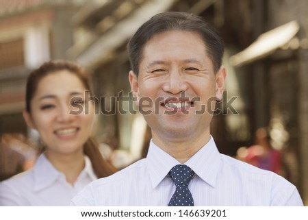 Portrait of two Business People, focus on businessman, outdoors, Beijing