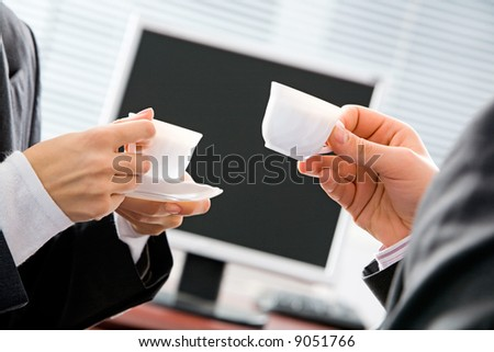 Portrait of two business people's hands holding cups on the background of screen - stock photo