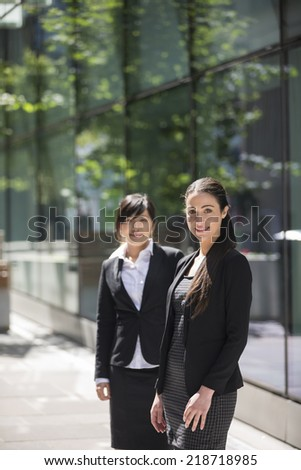 Portrait of two business women. Focus is on caucasian woman at the front. Interracial group of business women. - stock photo