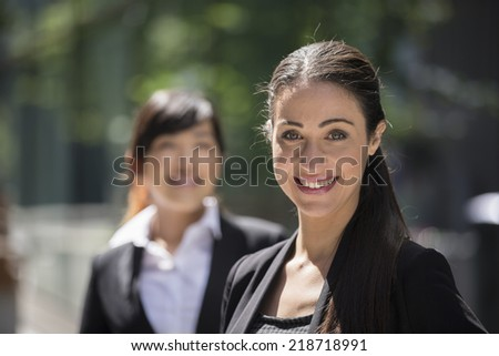Portrait of two business women. Focus is on caucasian woman at the front. Interracial group of business women.