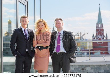 Portrait of two businessman and woman on the terrace overlooking Kremlin - stock photo