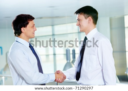 Portrait of two businessmen handshaking and greeting each other