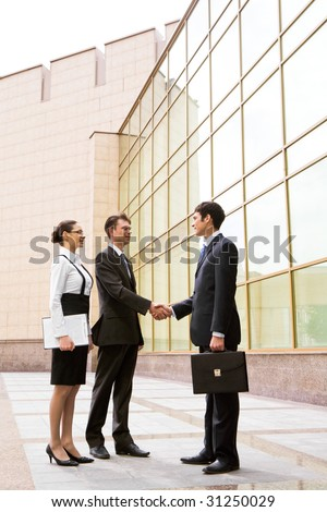 Portrait of two businessmen shaking hands after signing contract with pretty employee standing near by - stock photo