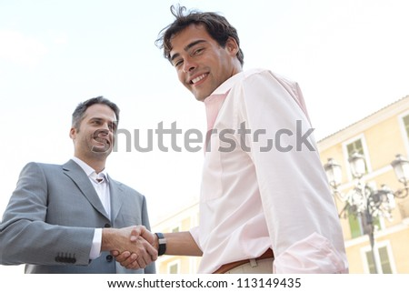 Portrait of two businessmen shaking hands while standing in front of a classic European building, outdoors.