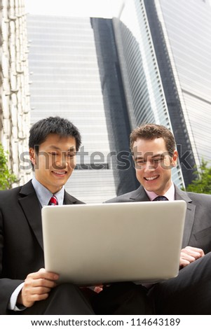 Portrait Of Two Businessmen Working On Laptop Outside Office - stock photo