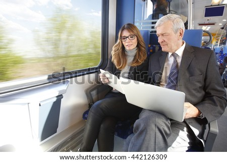 Portrait of two businesspeople traveling on train. Middle age businesswoman using digital tablet while senior businessman holding laptop in his hand and working together.  - stock photo