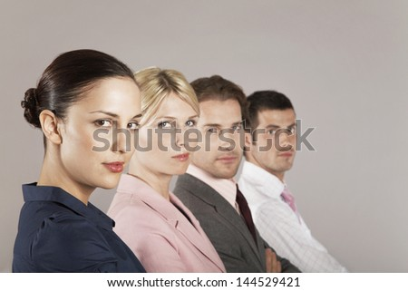 Portrait of two businesswomen and men in a row against colored background - stock photo
