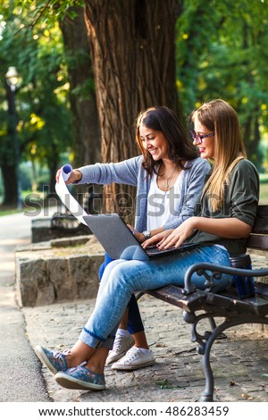 Portrait of two businesswomen sitting in park with laptop and blueprints. Business team working online togetherness while consulting.