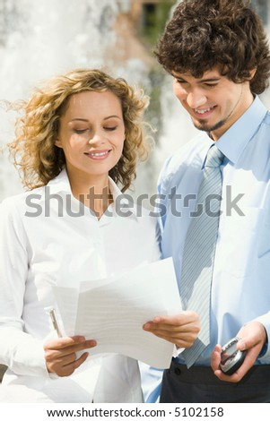 Portrait of two businesswomen  standing outside ahead of the fountain reading the contract