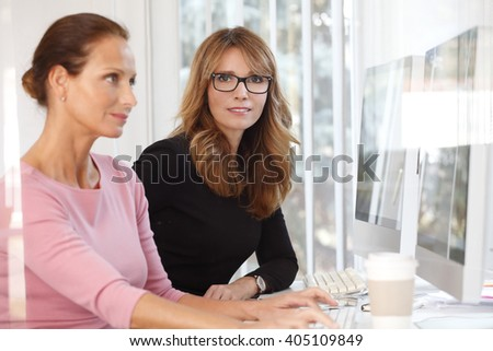 Portrait of two businesswomen talking together at a workstation in an office. - stock photo