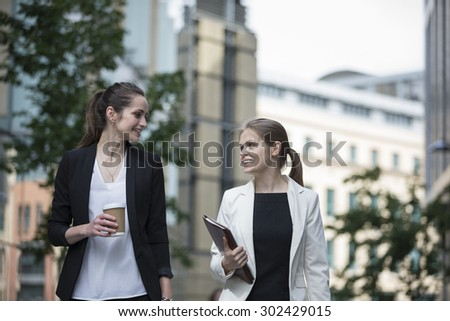 Portrait of two caucasian business women talking outside modern office building. - stock photo