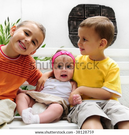 Portrait of two caucasian happy young boys with little baby girl sitting on a bench - stock photo