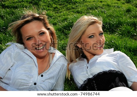Portrait of two charming girls on green grass