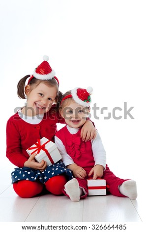 Portrait of two charming sisters in Christmas hat with gifts - stock photo