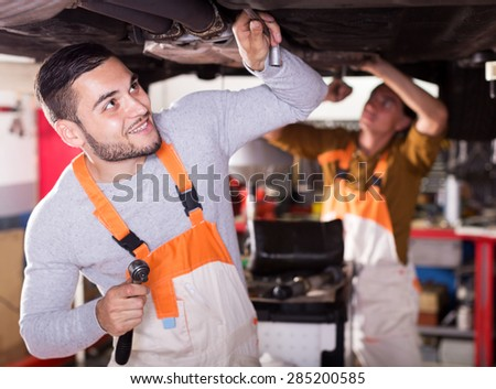 Portrait of two cheerful car mechanics at workshop at work - stock photo