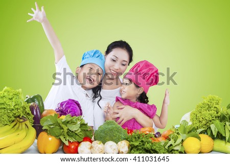 Portrait of two cheerful children and their mother preparing fresh vegetables, shot with green background