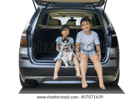 Portrait of two cheerful children sitting in the car with husky dog and smiling at the camera, isolated on white background - stock photo