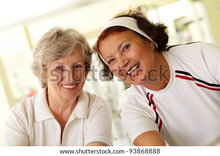 Portrait of two cheerful grandmas looking at camera with smiles - stock photo