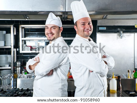 Portrait of two chefs standing back to back smiling and holding kitchen utensil - stock photo