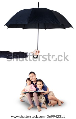 Portrait of two children sitting in the studio with their father while reading a book under umbrella - stock photo