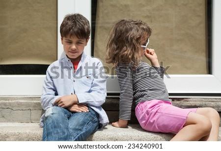 portrait of two children sitting on the sidewalk - stock photo