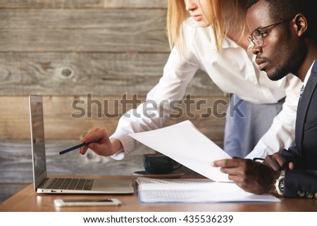 Portrait of two colleagues working together at a cafe, discussing business ideas and plans, using laptop computer: Caucasian woman holding a pen, pointing at the screen while presenting a project - stock photo