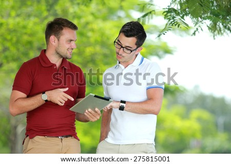 portrait of two college students discussing an assignment using tablet at college park - stock photo