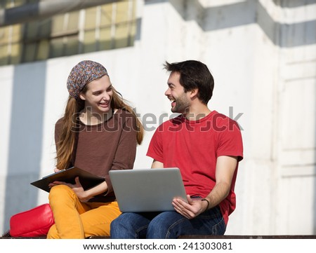 Portrait of two college students talking and working outdoors on laptop - stock photo