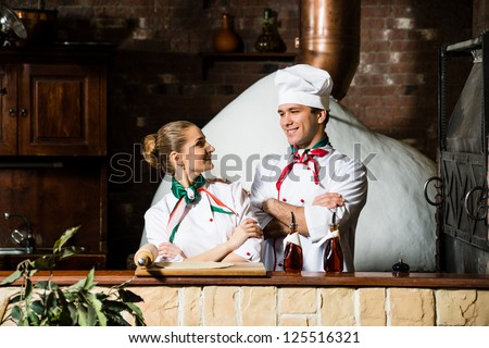 portrait of two cooks, crossing his arms and looking at each other - stock photo